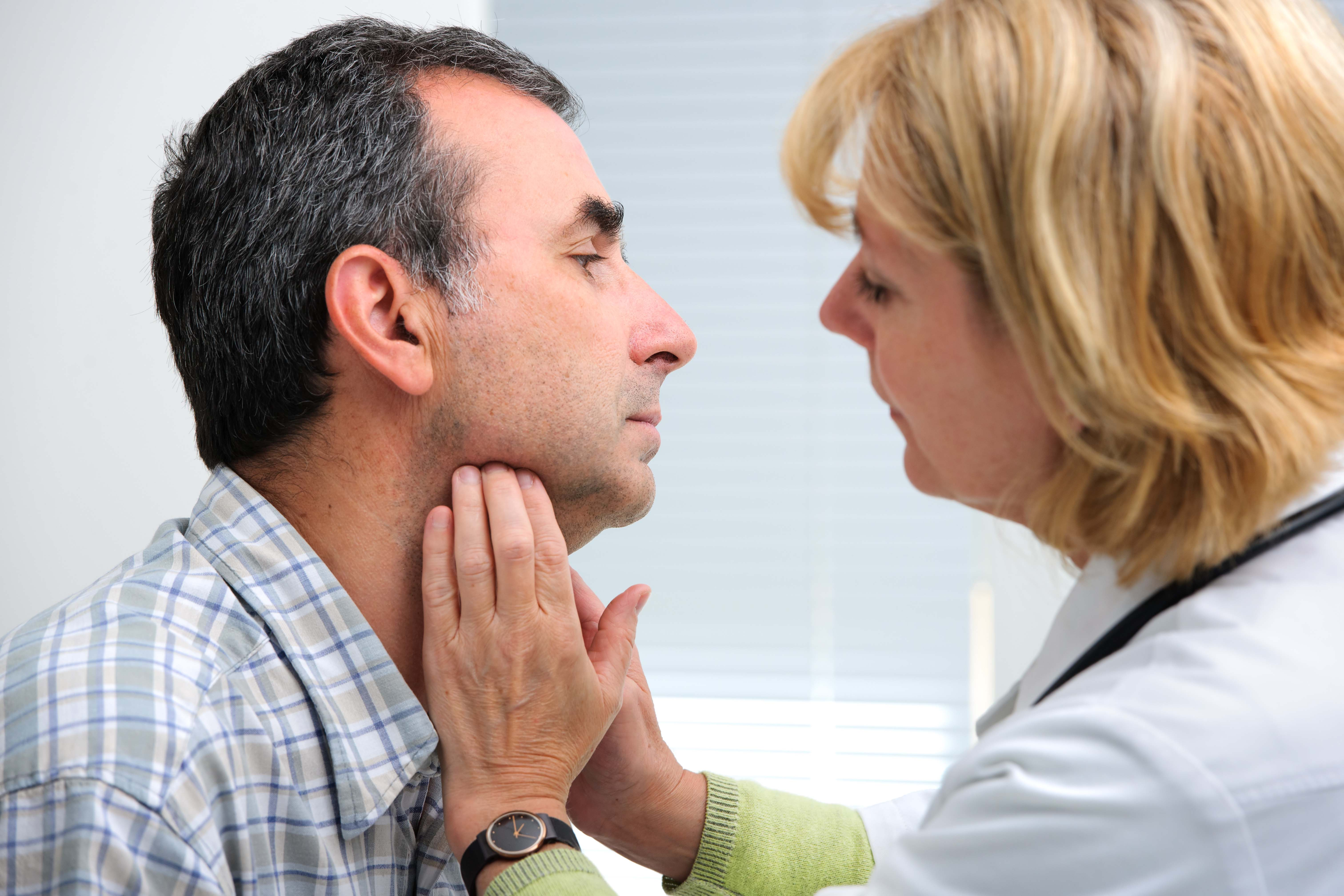 doctor checking mans throat